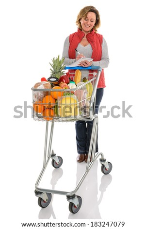 A woman with a supermarket trolley full of fresh food checking her shopping list, isolated on a white background. - stock photo