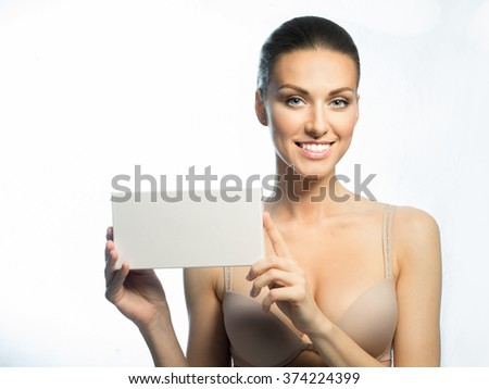 A woman with a wide smile, white teeth, silicone breasts and advertising card - stock photo