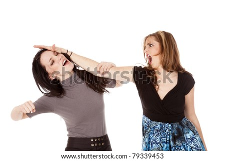 a woman with an angry expression on her face hitting another woman. - stock photo