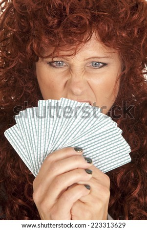 A woman with an upset expression on her face holding on to cards. - stock photo