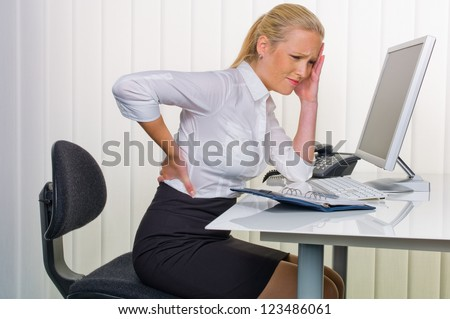 a woman with back pain from sitting so long in the office. health and welfare at work. - stock photo