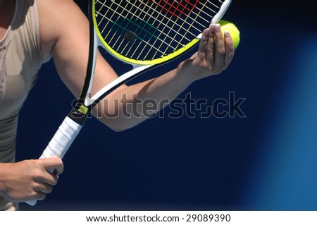 A woman with beautiful hands is holding a tennis ball and racquet preparing for her serve. - stock photo