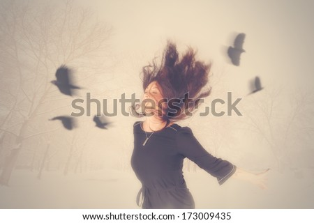 a woman with birds flying around her head - stock photo