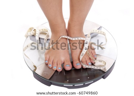 A woman with blue toenails is standing on the scales measuring her weight. - stock photo