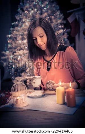 a woman with christmas lights and the christmas tree at home