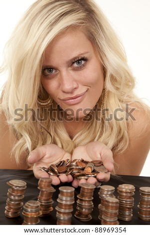 a woman with coins in her hands and stacked  with a small smile. - stock photo