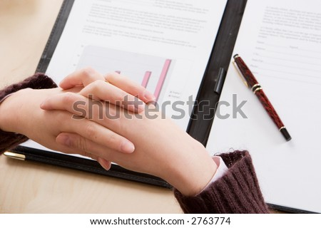 A woman with crossed hands reading through the latest financial figures