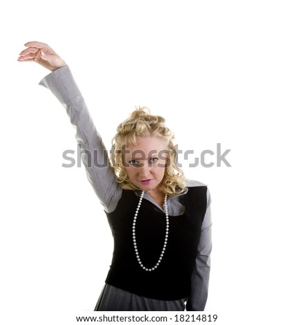 A woman with curly blond hair and pearls with one arm raised in air