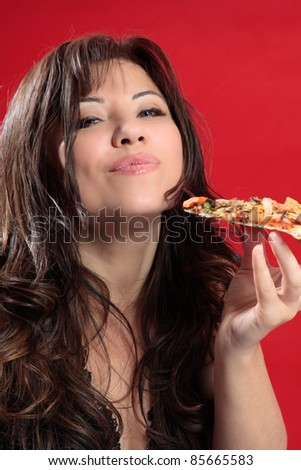 A woman with dark brown hair is enjoying delicious slice of italian pizza. - stock photo