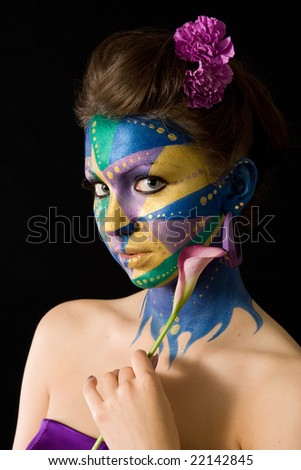 A woman with extreme full-face body painting poses on a black background holding a calla lily. Mardi Gras color theme. - stock photo