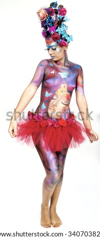 A woman with extreme full-face body painting poses on a white background. Carnival concept