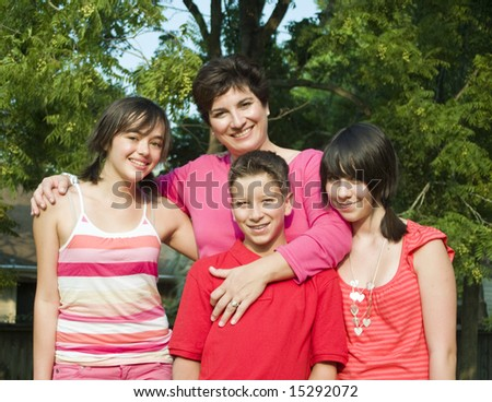 A woman with girls and a boy who appear to be her children. - stock photo