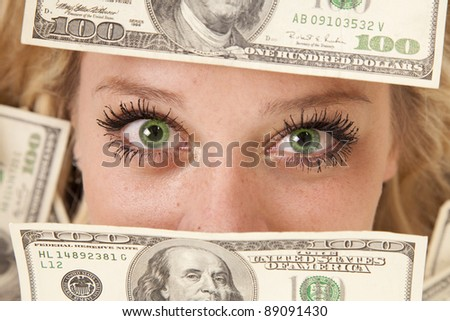 A woman with green eyes peeking through money - stock photo