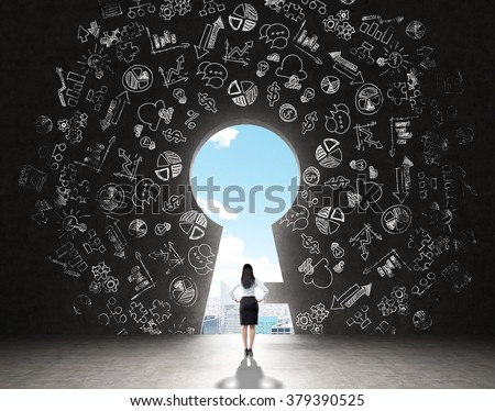A woman with hands on hips standing in front of a huge keyhole, many business icons drawn around it, city and sky seen through it. Black background. Back view.  Concept of finding the way - stock photo