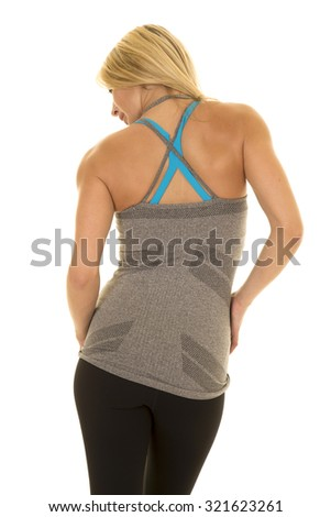 a woman with her back to the camera in her fitness clothing. - stock photo