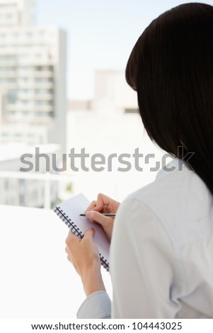 A woman with her back to the camera starts writing on her notepad - stock photo