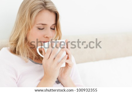 A woman with her eyes closed, in bed with a cup raised to her nose to take in the smell of the cups aroma. - stock photo