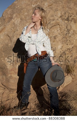 A woman with her eyes closed in her western outfit holding on to her hat. - stock photo