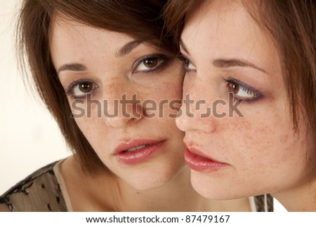 a woman with her face up against the mirror looking at herself. - stock photo