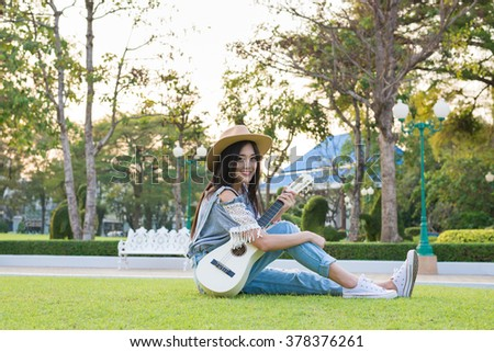 a woman with her guitar down, sitting on playground - stock photo