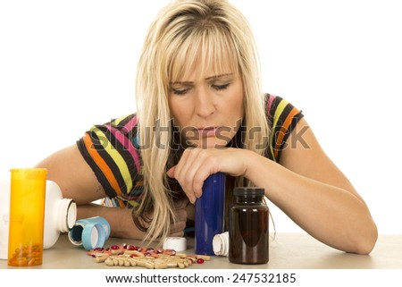 A woman with her hand on top of the bottle looking at the pills. - stock photo