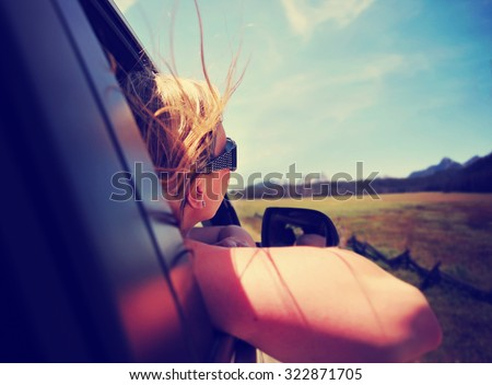 a woman with her head out the window enjoying a scenic drive through the sawtooth mountain range in idaho along an old highway toned with a retro vintage instagram filter app or action effect - stock photo