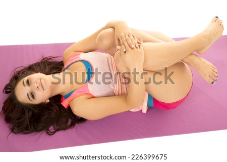A woman with her legs up stretching out her back.
