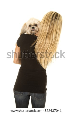 a woman with her puppy over her shoulder looking.