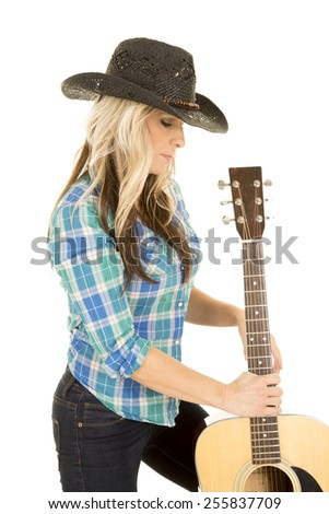 A woman with her western hat on looking down at his guitar. - stock photo