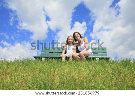 A woman with his child sitting on the bench - stock photo