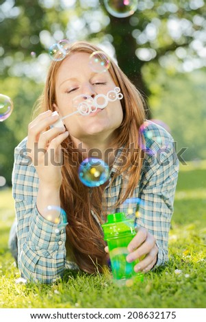 A woman with long red hair making soap bubbles in a summer park. - stock photo