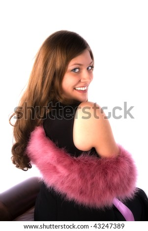 A woman with looking over her shoulder with a smile on her face with her pink fuzzy scarf. - stock photo