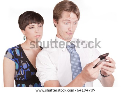 A woman with mad expression on her face looking over the mans shoulder while he is texting. - stock photo