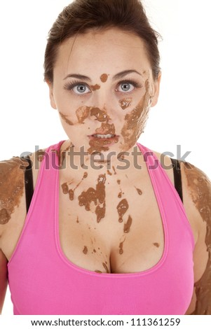 A woman with mud on her shoulders and face with a serious expression on her face. - stock photo