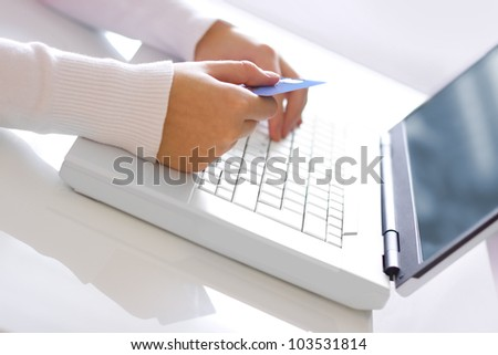A woman with payment card. On-line shopping on the internet using a laptop.
