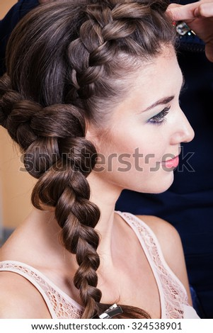 a woman with plait in the barbershop - stock photo