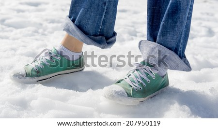 A woman with street shoes and pants rolled up having fun in the snow