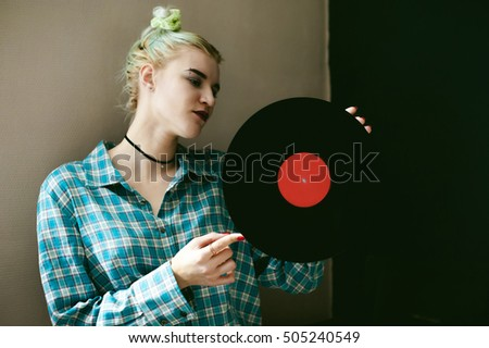 a woman with the disc. young beautiful hipster girl with old vintage vinyl record in his hands. she wants to listen to music on old player