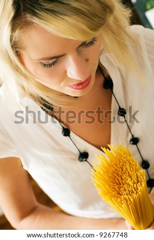 A woman with uncooked spaghetti (going to prepare them presumably) - stock photo