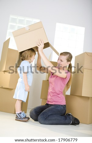 A woman with young girl are between cardboard boxes. A woman taking off cardboard box from head young girl. - stock photo