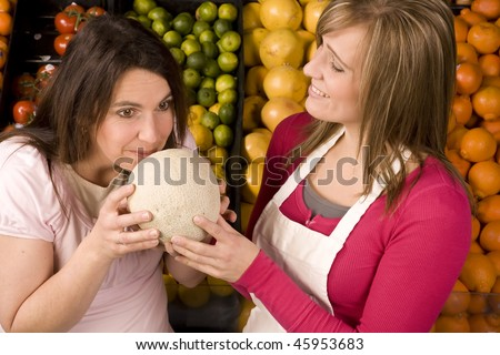 A woman working at the grocery store having a customer smell a cantalope for freshness.