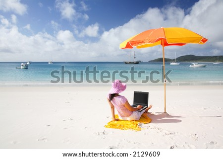 A woman working on the beach in Whitsunday island - stock photo