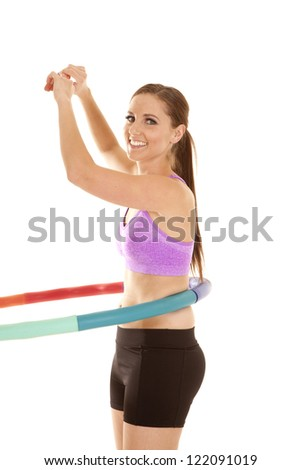 A woman working out with a weighted hoola hoop. - stock photo