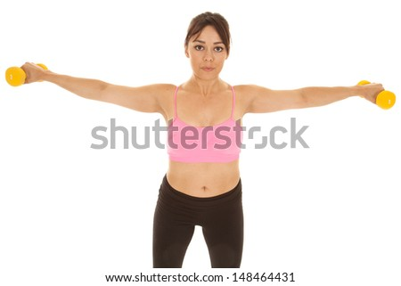 A woman working out with weights holding out her arms to strengthen her shoulders.