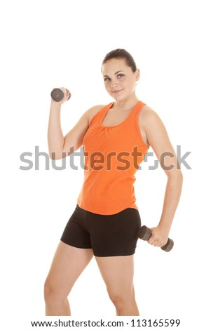 A woman working out with weights with a small smile on her face. - stock photo