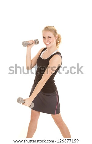 A woman working out with weights, with a smile on her face.