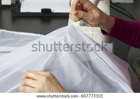 A woman works on a sewing machine. She sews the curtains on the window. Pulls the thread from the fabric to mark and cut off excess.