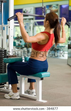 A woman works out at a back station in a heath and fitness center