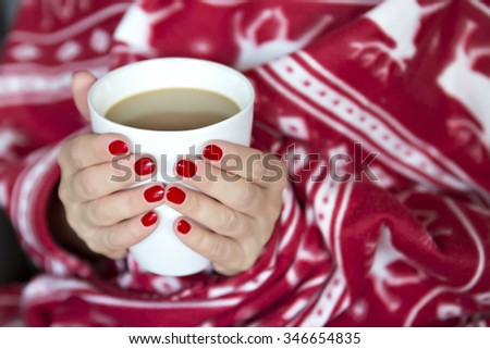 A woman wrapped in a blanket with a cup of hot drink