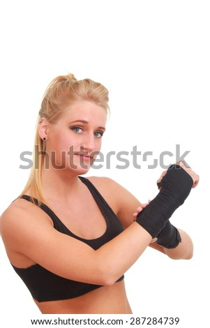 A woman wrapping her hand for a fight workout - stock photo